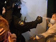 Сотрудник ОМОНа применяет баллончик со слезоточивым газом против участника акции протеста в Минске