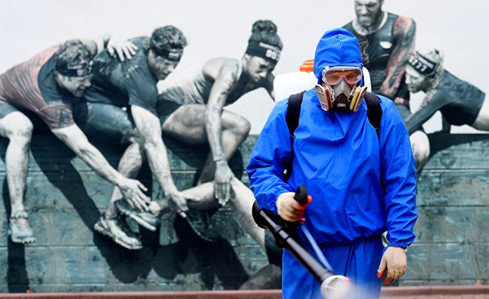 Сотрудник санитарной службы проводит дезинфекцию в Парке Победы в Москве