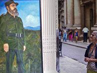 Женщина смотрит на фреску, изображающую Фиделя Кастро на одной из улиц Гаваны
