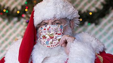 Санта-Клаус поправляет маску в торговом центре в Нью-Йорке