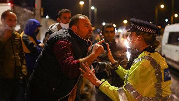 Мужчина спорит с полицейским , ожидая посадки на паром в Дувре
