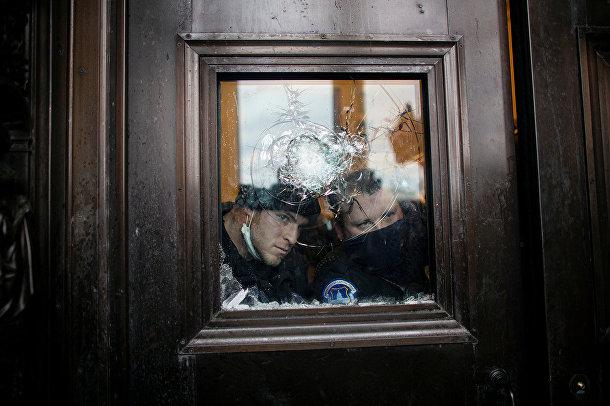 Сотрудники полиции наблюдают за протестующими в здании Капитолия США в Вашингтоне