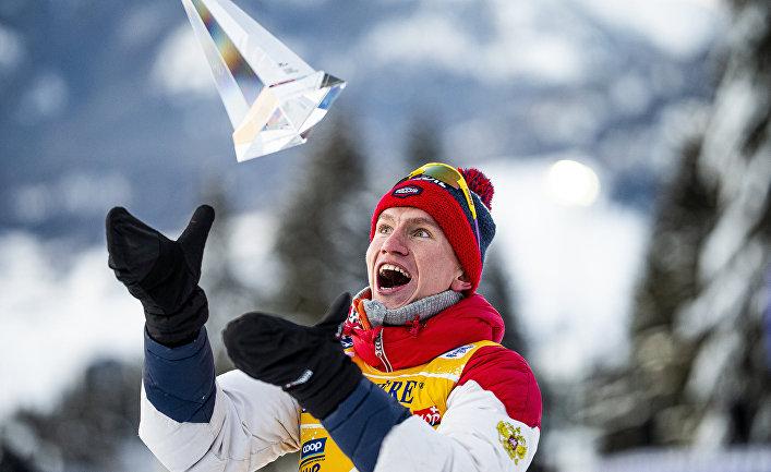 Александр Большунов (Россия), занявший первое место вобщем зачете насоревнованиях полыжным гонкам «Тур деСки» среди мужчин витальянском Валь-ди-Фьемме, нацеремонии награждения