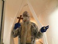 Священник в защитном костюме посещает пациентов коронавирусного отделения больницы во Львове, Украина