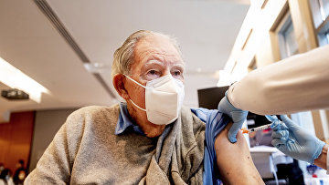 Пожилому мужчине делают прививку вакциной Pfizer
