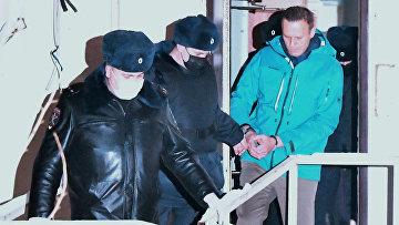 Сотрудники полиции выводят А. Навального из здания отдела полиции Управления МВД России по г. Химки, где прошел суд