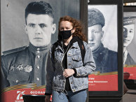 Женщина в маске идет мимо плакатов с портретами солдат Великой Отечественной войны