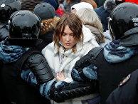 Полицейские держат участницу протестов в Москве