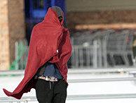 Мужчина в одеяле во время аномальных холодов в Хьюстоне, Техас, США