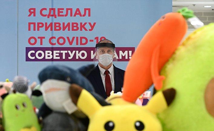 Сотрудник торгового центра «Европейский» возле агитплаката упункта вакцинации откоронавируса
