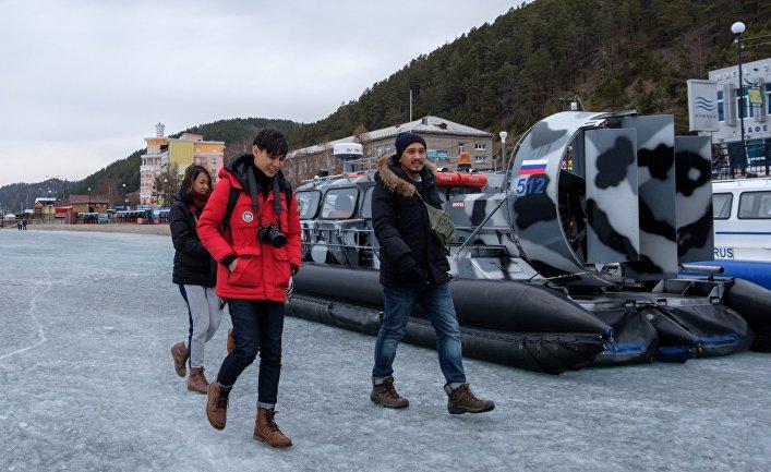 Туристы на льду озера Байкал в поселке Листвянка