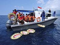 Люди бросают цветы с именами членов экипажа затонувшей подводной лодки Nanggala-402 во время молитвы на море