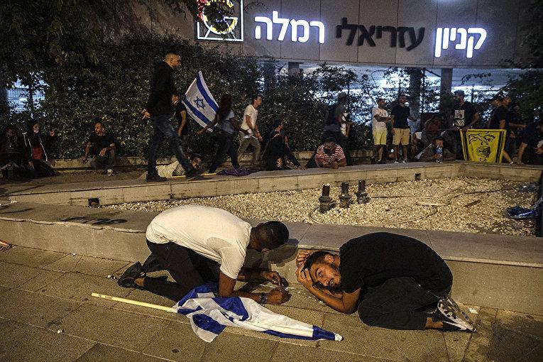 Местные жители укрываются во время шквала ракет, выпущенных из сектора Газа в израильском городе Рамла