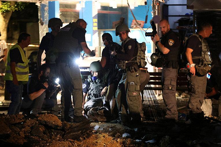 Сотрудники сил безопасности на месте взрыва ракеты, запущенной из сектора Газа