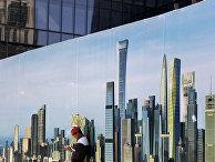 Рабочий у стены строительной площадки с изображением небоскребов в центральном районе Пекина