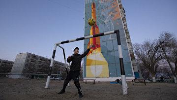 Мальчик играет в футбол на спортивной площадке в городе Байконур, Казахстан