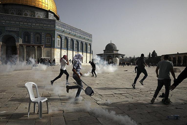 Палестинцы во время столкновений с израильскими силами безопасности у мечети Аль-Акса в Иерусалиме
