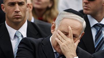Премьер-министр Израиля Биньямин Нетаньяху закрывает лицо во время церемонии в День памяти жертв Холокоста в мемориальном комплексе Яд Вашем в Иерусалиме