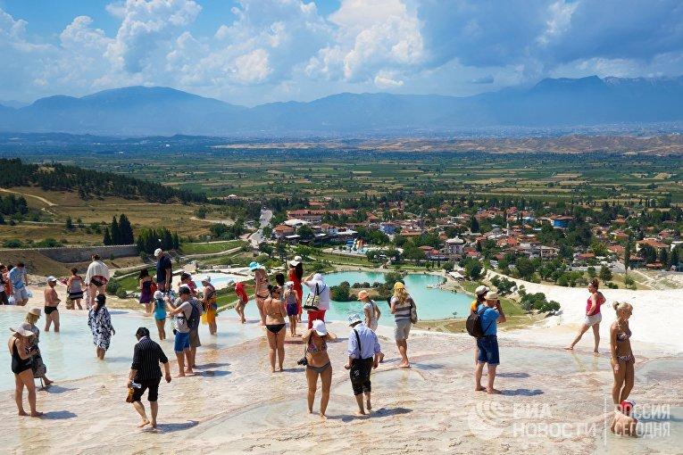 Туристы втравертинах— природных известковых бассейнах вПамуккале наюго-западе Турции