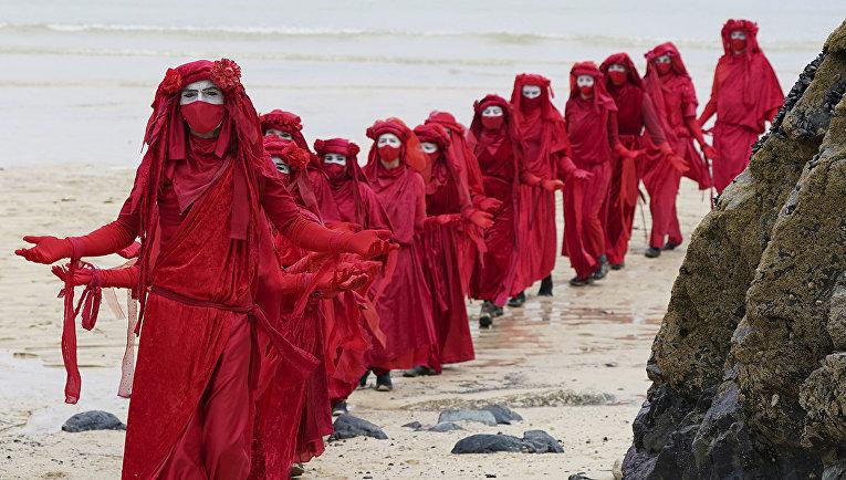 Участники акции протеста на пляже в Сент-Айвсе, Корнуолл, Великобритания