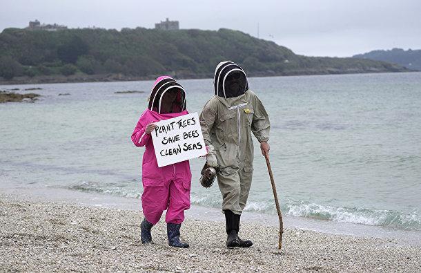 Климатические активисты на пляже в Фалмуте, Корнуолл