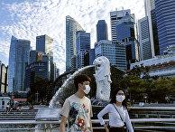 Прохожие у статуи Мерлайона в Сингапуре