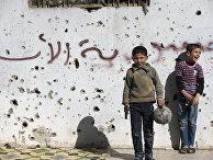 Сирийские мальчики играют в футбол возле разрушенных зданий в городе Хомс