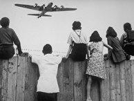 1 августа 1948. Дети из Западного Берлина смотрят, как в аэропорту Темпельхоф заходит на посадку самолет с продовольствием