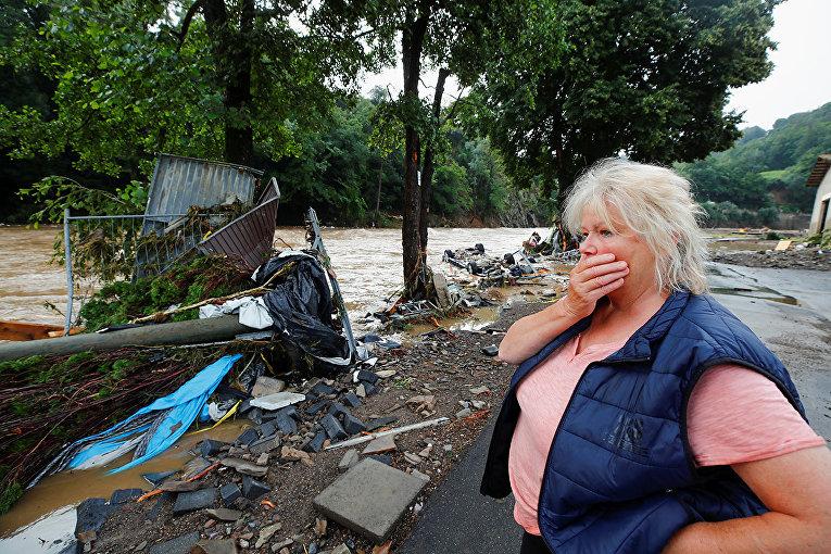 Местная жительница осматривает последствия сильного наводнения в Шульде