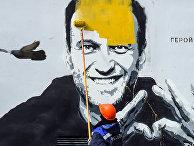 Рабочий закрашивает граффити с изображением Алексея Навального