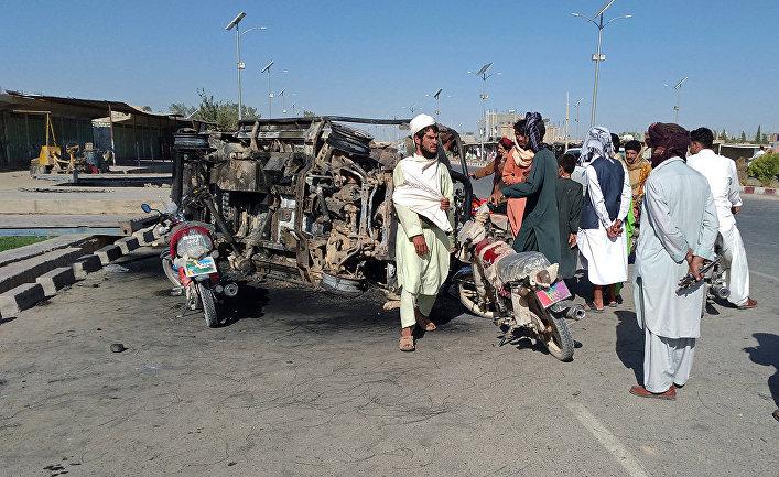Афганцы возле сгоревшего автомобиля в городе Фарах, Афганистан