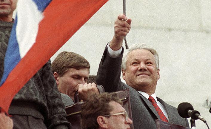 Президент России Б. Н. Ельцин стоит на трибуне с флагом