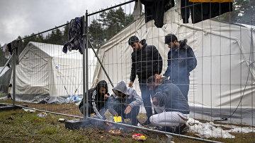 Мигранты готовят еду в лагере беженцев на военном полигоне Руднинкай, Литва