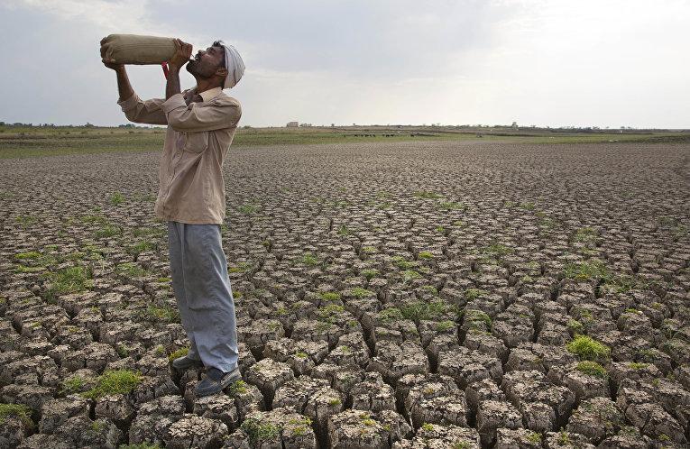 Мужчина на высушенной плотине Manjara Dam в Индии. 2016 год
