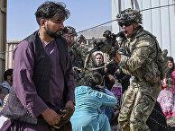 Американский солдат целится в афганцев в аэропорту Кабула