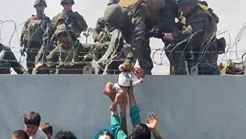 Афганцы передают ребенка американским солдатам через стену аэропорта в Кабуле, Афганистан