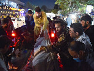 Волонтеры и медицинский персонал выгружают тела после двух мощных взрывов возле аэропорта в Кабуле