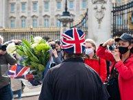 Люди несут цветы к Букингемскому дворцу в Лондоне