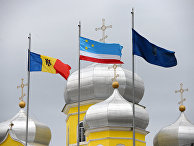 Флаги Молдовы и Гагаузии рядом с русской православной церковью в городе Комрат