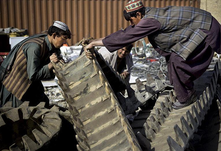 Афганские торговцы грузят резиновые гусеницы американского танка на юге Афганистана