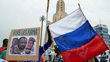 Малийцы держат фотографию полковника Ассими Гоиты и российский флаг