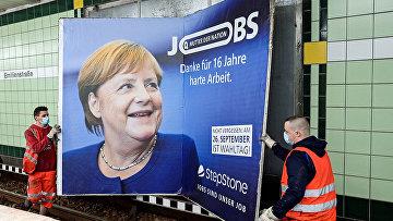Рабочие снимают плакат с изображением канцлера Германии Ангелы Меркель