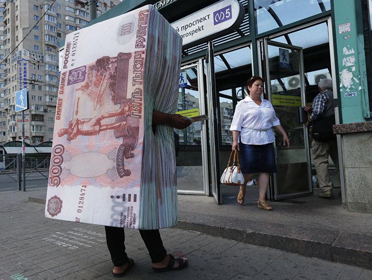 Человек в костюме пачки пятитысячных банкнот раздает флаеры у выхода из метро в Санкт-Петербурге